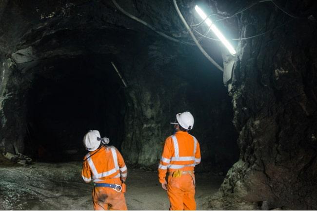Två gruvarbetare tittar uppåt och observerar gruvan. Foto: