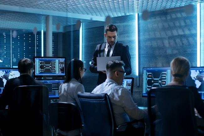 Personer arbetar framför datorer på mörkt kontor