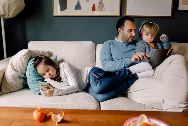 Barn ligger i soffan med telefon och pappa sitter med surfplatta tillsammans med mindre barn