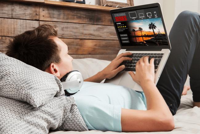 man streamar serier på en bärbar dator, liggandes i sängen