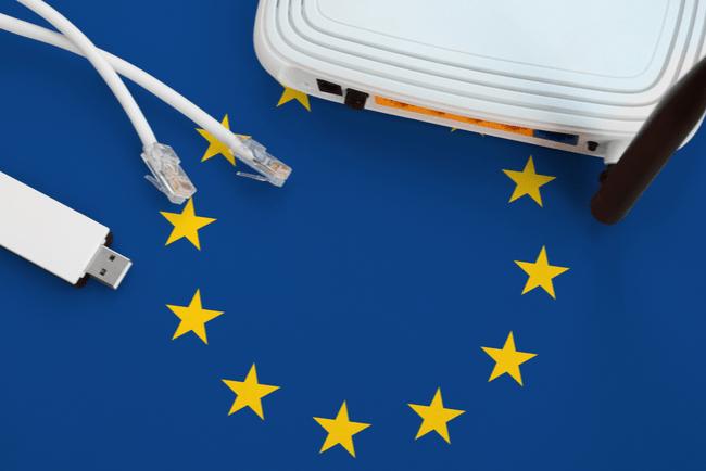 router, internetkablar och adapter med eu-flaggan i bakgrunden