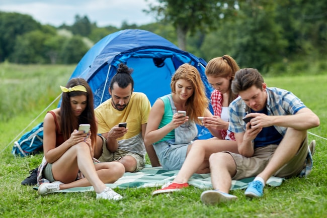 Tre tjejer och två killar sitter på en filt på en gräsmatta framför ett tält och surfar på sina mobiler.
