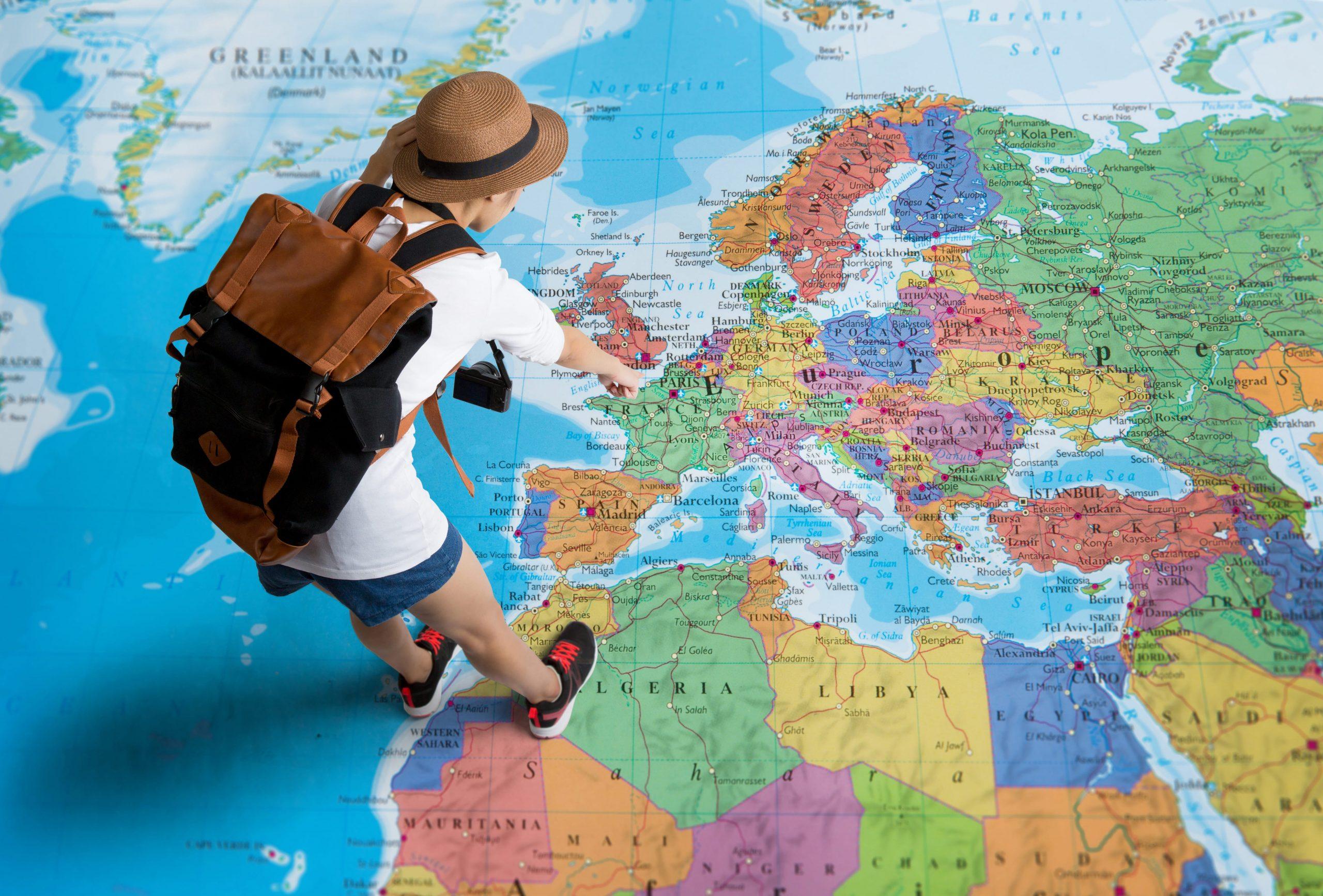 resenär står på världskarta och pekar på Europa
