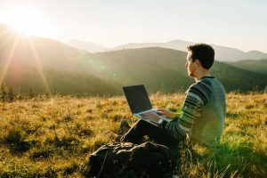 man sitter med laptop med utsikt över berg