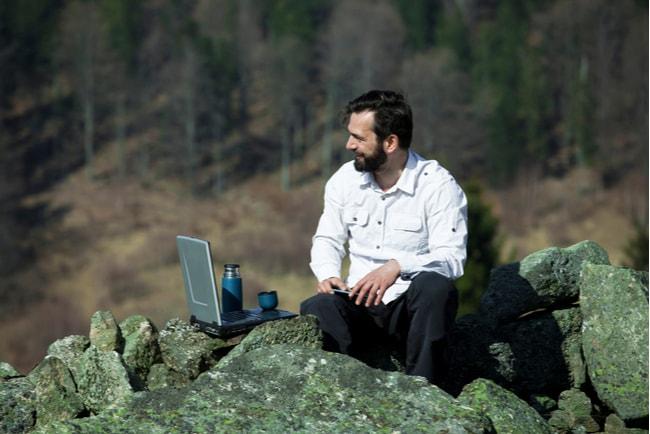 man sitter på berg med laptop
