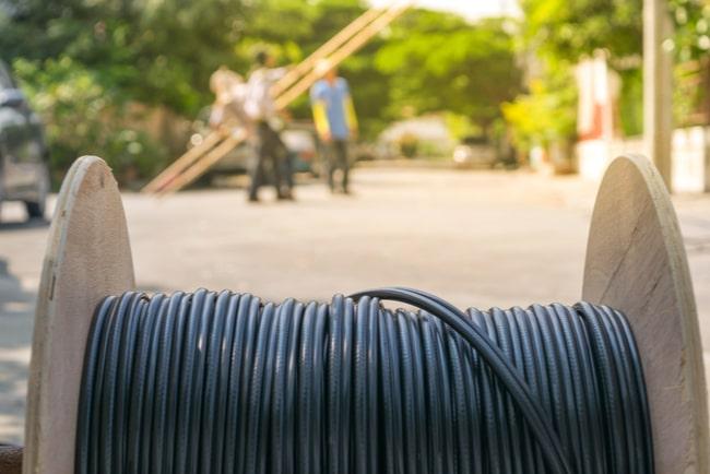 rulle med fiberkabel i förgrunden och installatörer som arbetar i bakgrunden