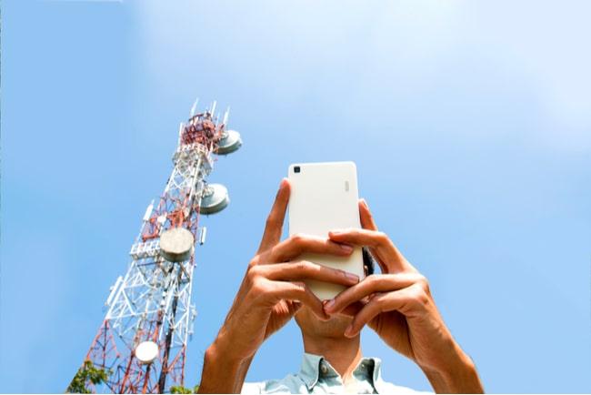 man håller mobil framför teletorn