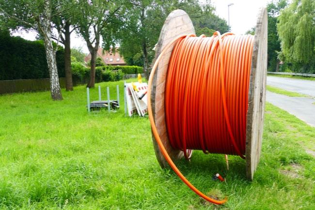 rulle med bredbandskablar ligger på gräsmatta i bostadsområde