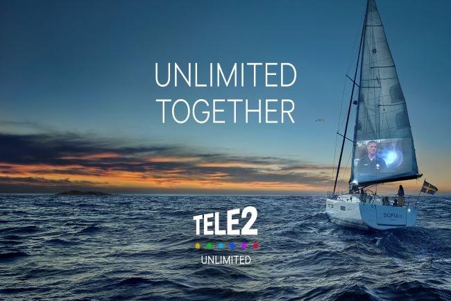 Tele2:s logotyp och texten obegränsade tillsammans mot bakgrund av hav, solnedgång och segelbåt