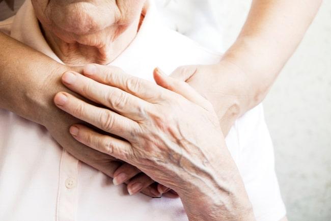Närbild på yngre kvinna håller om äldre kvinna.