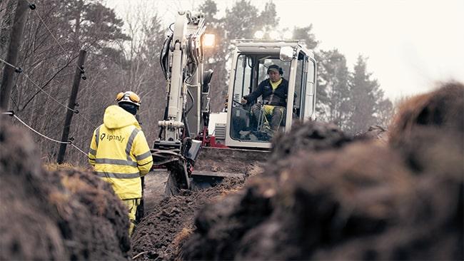 Byggarbetare från ip-only i gula arbetskläder står vänd mot grävskopa.